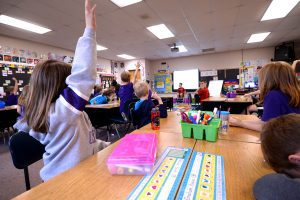 Elementary students with hands raised 3 rgb